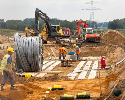 Europa, Deutschland, Nordrhein-Westfalen, Raesfeld, Baustelle des Netzbetreibers Amprion, der hier die bundesweit erste 380 kV-Hochspannungsleitung im Erdreich verlegt. Das Pilotprojekt, bei dem auch die Auswirkungen des magnetischen Feldes des Hochspannungsstroms auf den Pflanzenwuchs untersucht werden sollen, wird drei Kilometer lang sein und stellt einen von drei geplanten Testabschnitte auf der 130 Kilometer langen Trasse zwischen Meppen und Wesel dar. Die unterirdischen Kabel gelten als Alternative beim Bau neuer Stromtrassen, sind aber teurer als Strommasten und Ueberlandleitungen. -   Europe, Germany, North Rhine-Westphalia, Raesfeld, construction site of the network operator Amprion, who installed the nation's first underground 380 kV high-voltage line.  It is a pilot project in which the effects of the magnetic field of high voltage current on plant growth will be tested. It will be three kilometers long and is one of three test sections of the 130 km-long route between Meppen and Wesel. The underground cables are considered to be an alternative for the construction of new power lines, but are more expensive than electricity pylons and overland lines.